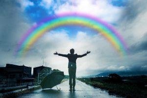 両腕を広げる人と虹